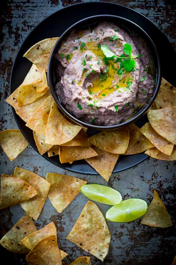 Black Bean Hummus. With lime, cilantro and garlic served with home-made baked tortilla chips. It is a healthy and yummy snack or appetizer. Great for the Super Bowl or party. Healthy Seasonal Recipes.