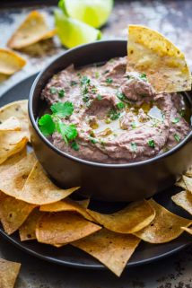 a black bowl with black bean hummus and tortilla chips