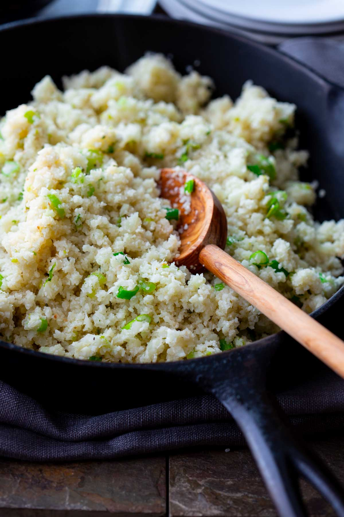 a skillet with cauliflower rice in it and a wooden spoon