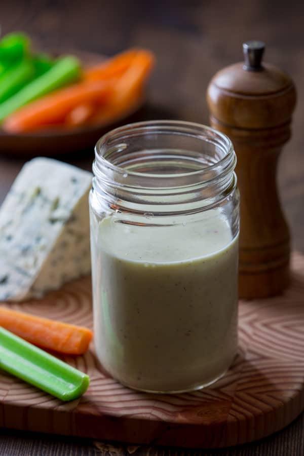 greek yogurt blue cheese dressing in jar on cutting board