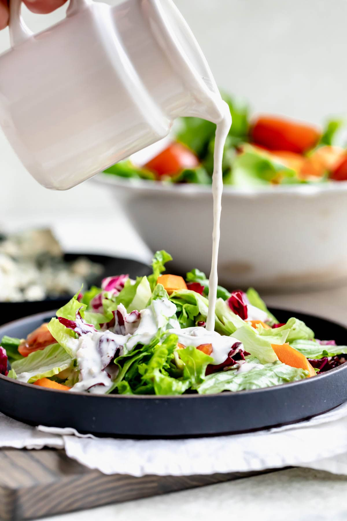 a pitcher of dressing pouring over a plate of salad