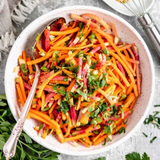 carrot and radish slaw in a white bowl from overhead