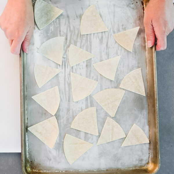 tortilla wedges spread on baking sheet