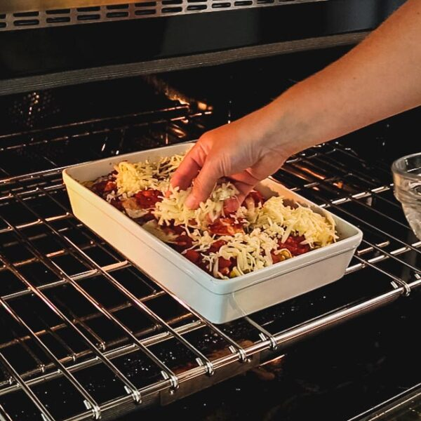 topping casserole with cheese in the oven