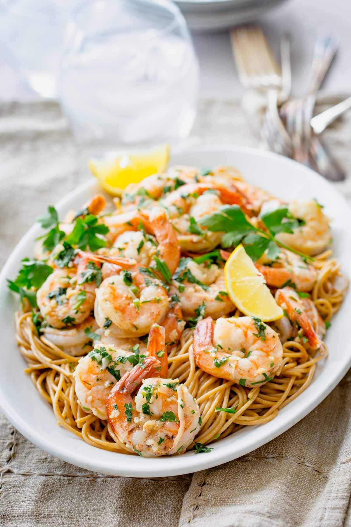 shrimp over pasta on a white platter
