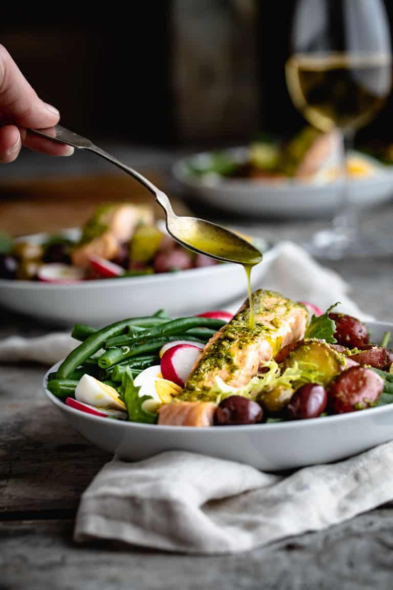 Salmon Nicoise Salad topped with hard boiled eggs, green beans, olives, potatoes and radishes. The pesto is smothered in pesto and baked then set atop for a fresh and healthy version of salad Niçoise. #salmon #nicoise #saladnicoise #salad #healthy