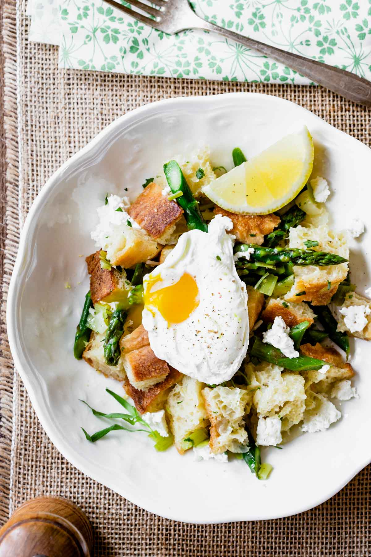 overhead of panzanella with a poached egg in a white bowl