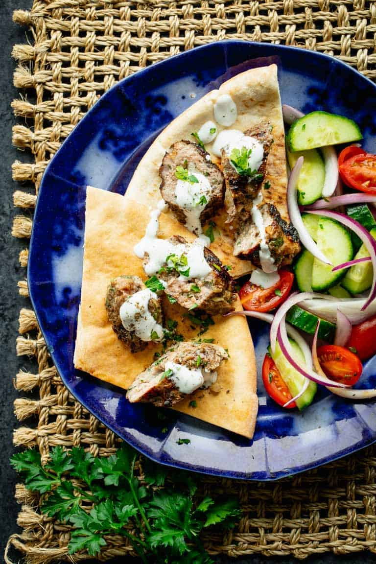 kofta made into a pita sandwich with yogurt