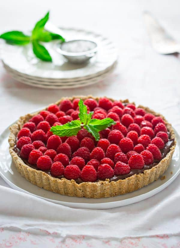 Hazelnut Crust made with whole-wheat flour and coconut oil, filled with dark chocolate filling and topped with fresh raspberries!