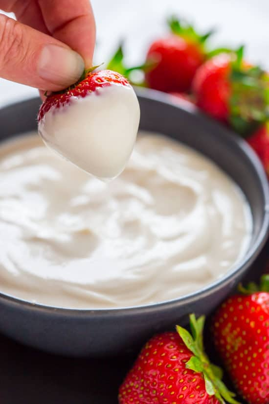 dipping a strawberry into maple greek yogurt dip