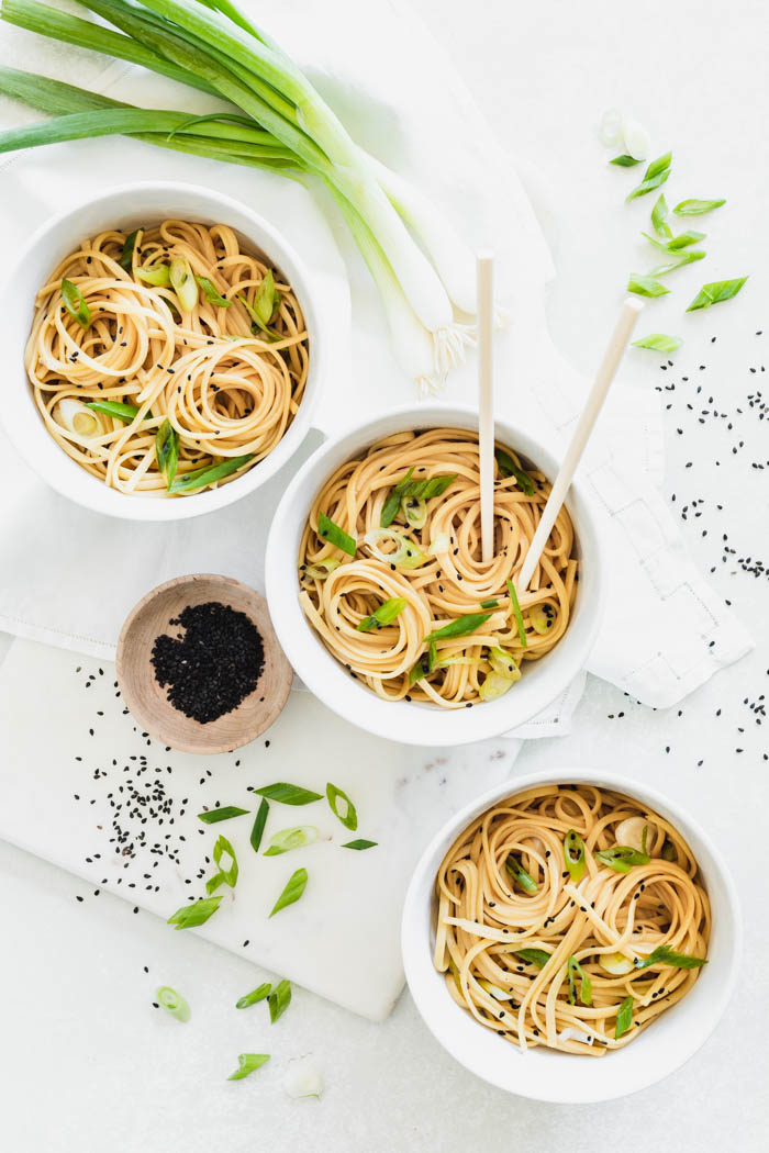 sesame noodles in a three bowls on a white table