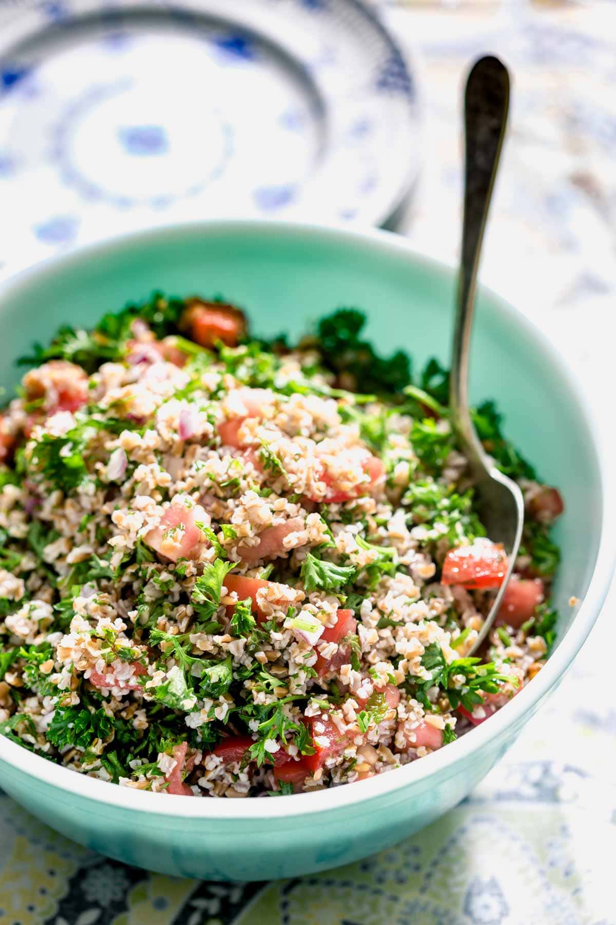 a teal bowl with tabbouleh in it