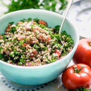 side view of a teal bowl with tabbouleh in it