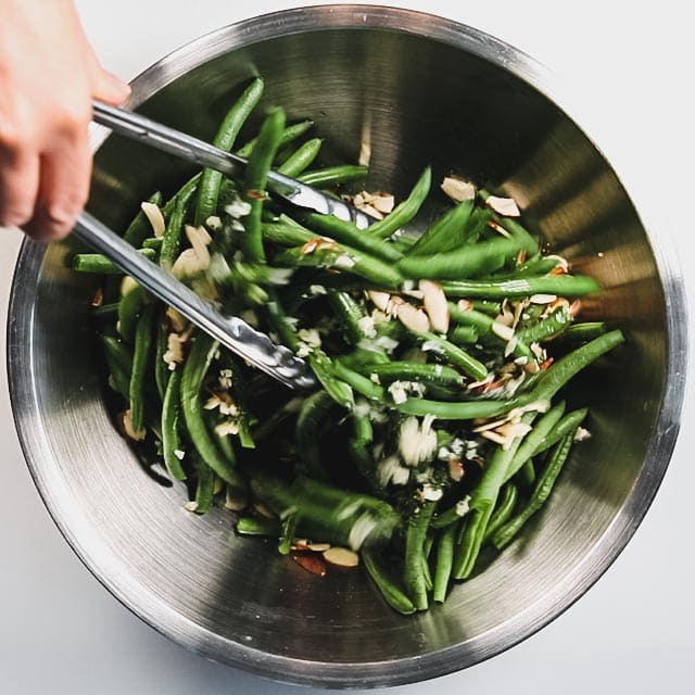 stirring the green beans in a bowl with tongs
