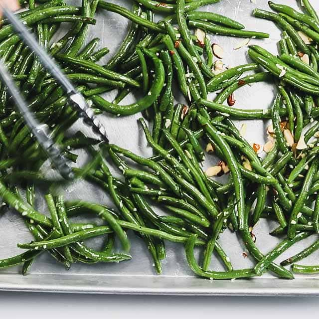 spreading the green beans on a sheet pan
