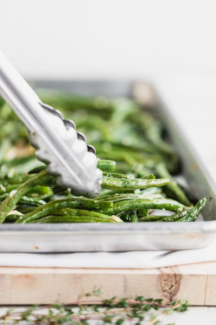 a pan of green beans from the side with a set of tongs grabbing a few