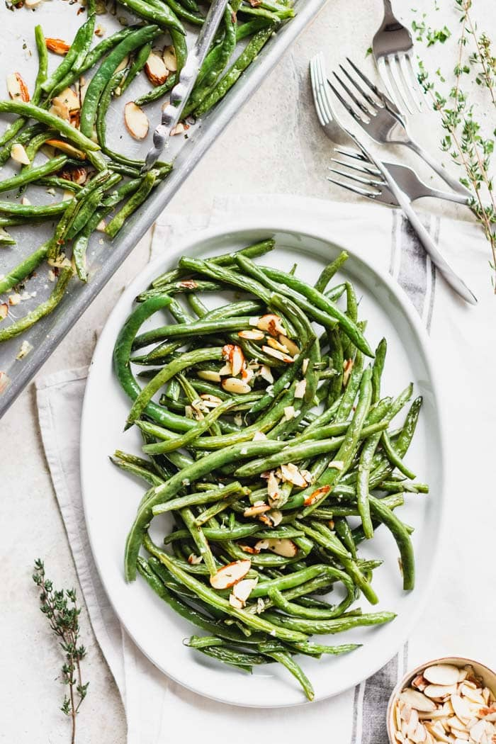 a platter of roasted green beans with a tray of roasted green beans next to it
