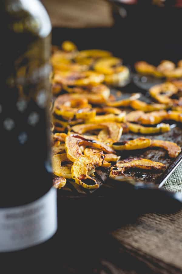 Roasted Delicata Squash on tray next to wine bottle