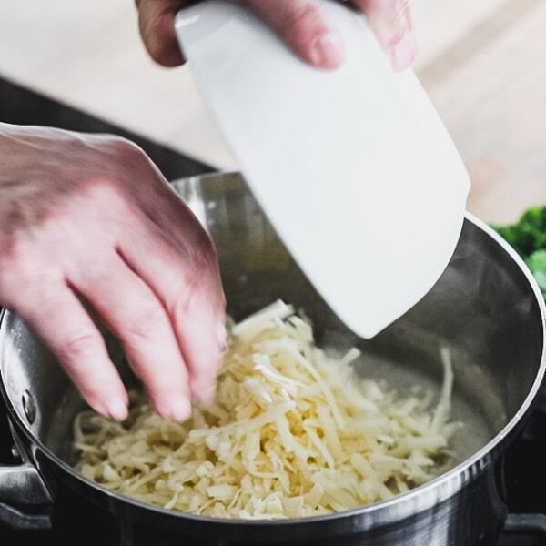 adding cheese to the sauce