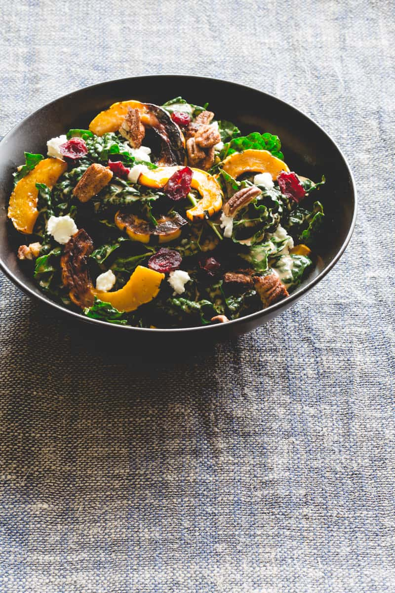Photo of a kale salad with feta, sweet potato, dried cranberries, and walnuts.