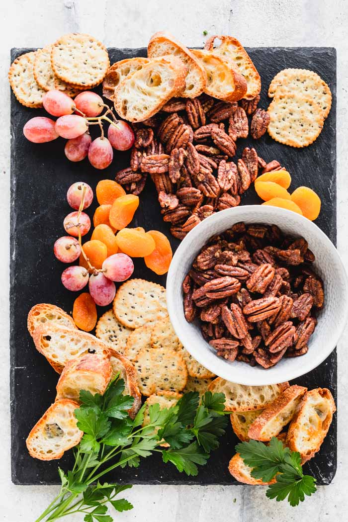 spiced nuts on a black slate with grapes, crostini and apricots
