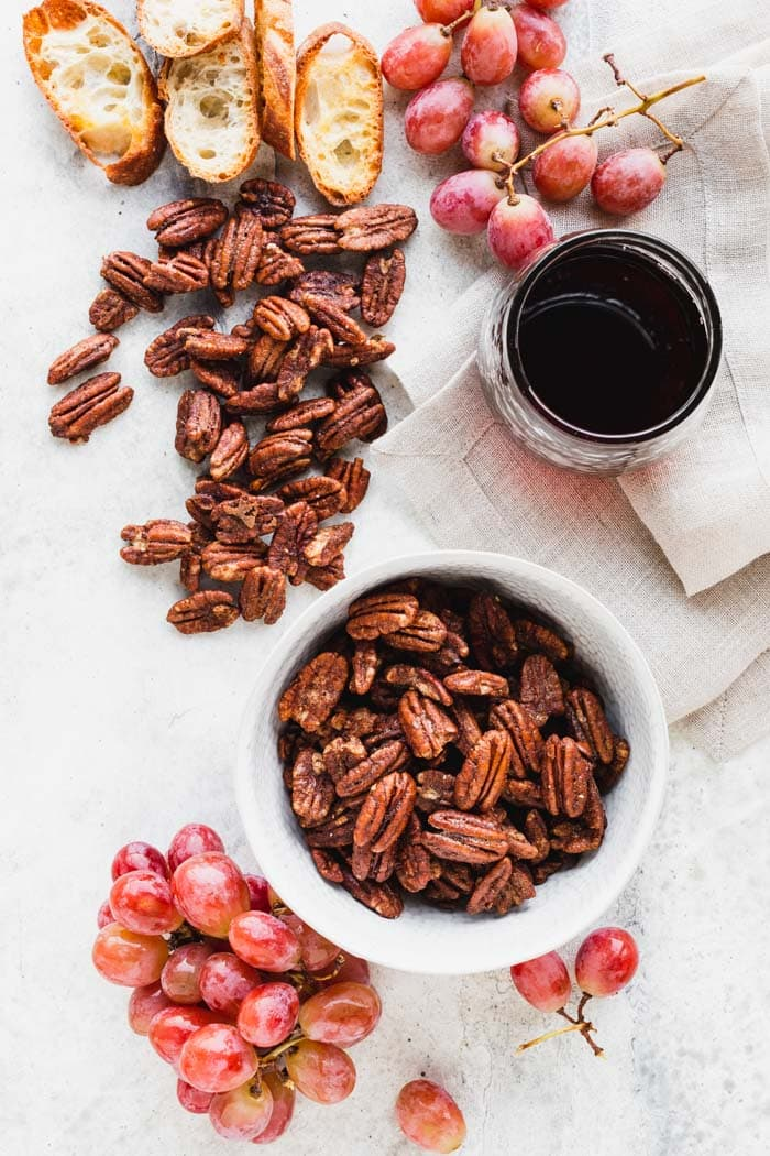 a white table with spiced pecans spilled out over it