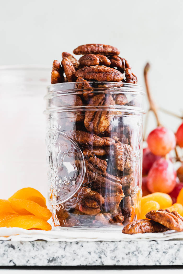 a jar from a low angle filled with spiced nuts. Grapes and apricots are in the background