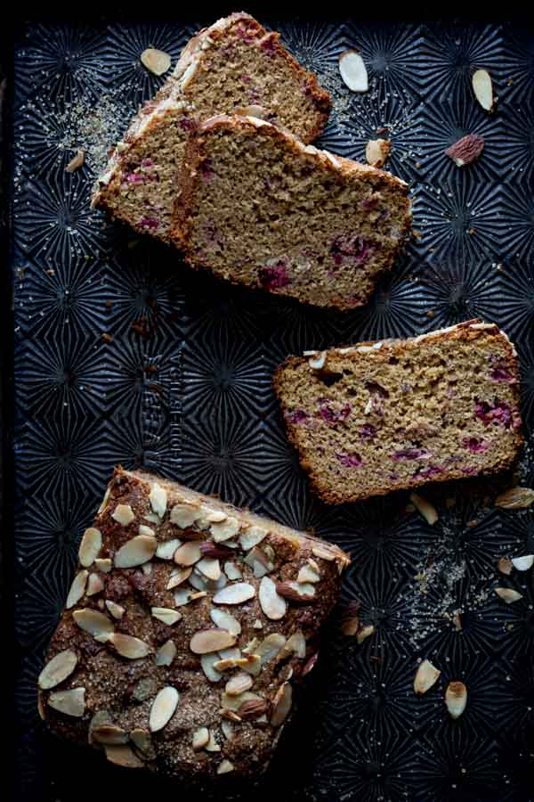 almond cranberry bread slices next to loaf