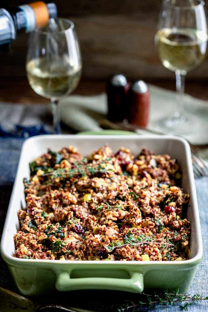 a table with white wine and a baking dish of gluten-free quinoa stuffing