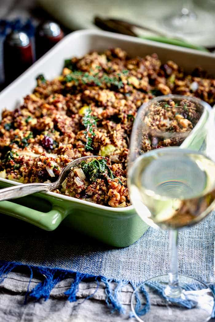 a glass of white wine with a baking dish of quinoa stuffing on a blue placemat