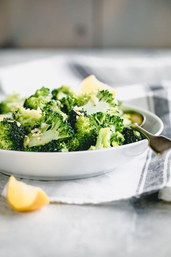 Lemon Garlic broccoli in a white bowl from the side