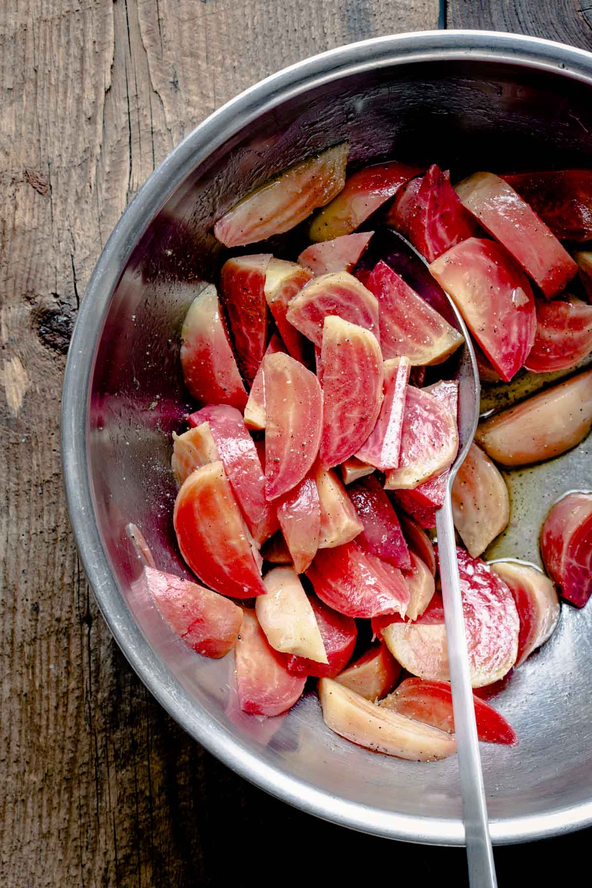 Chioggia beets in a stainless bowl with vinegar, oil and salt and pepper.