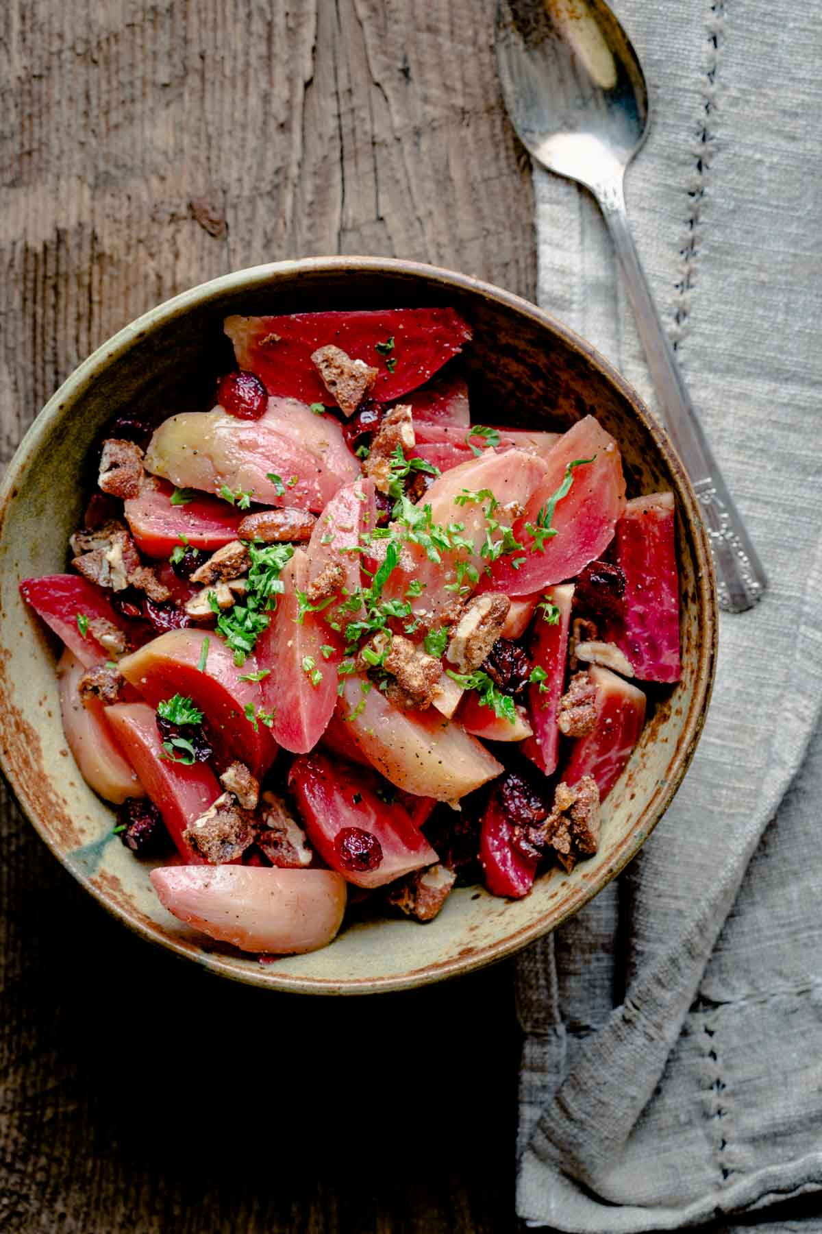 beets with spiced nuts in a ceramic bowl on a wooden tabletop