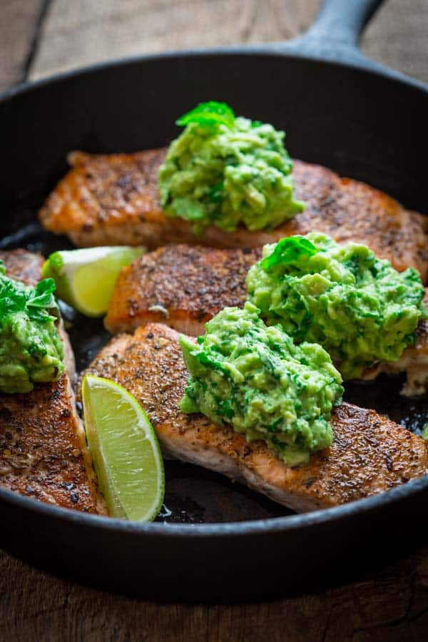skillet salmon with lime wedges and mashed avocado