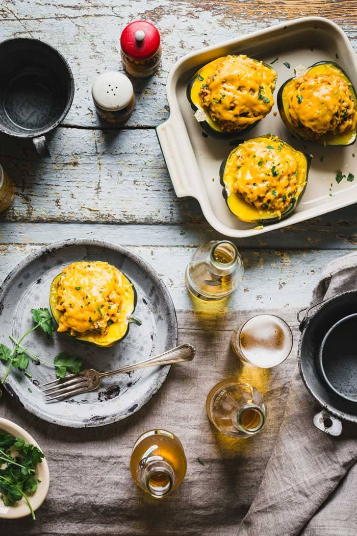 Stuffed acorn squash from overhead on a table with beer and cilantro