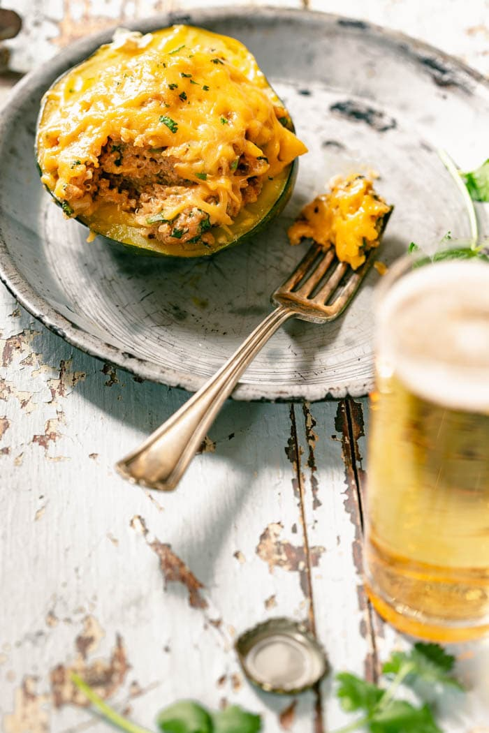 Stuffed Acorn Squash on a metal plate with a fork sitting on the plate