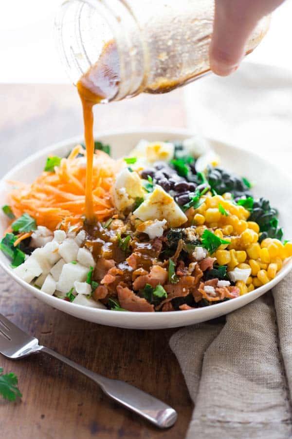 pouring dressing onto a Southwest Cobb Salad