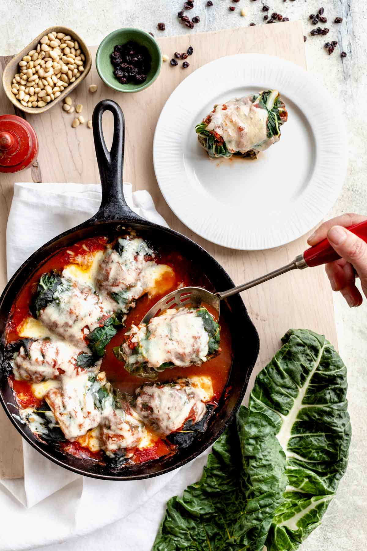 swiss chard rolls in a skillet, one is on a plate and another is being lifted up on a slotted spoon