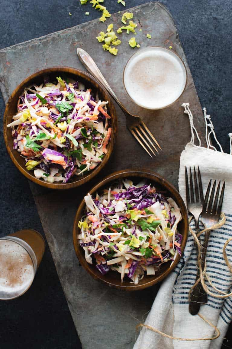 An overhead view of two wooden bowls of coleslaw and two glasses of beer