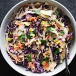 A close up of a white serving bowl of brightly colored cabbage based coleslaw