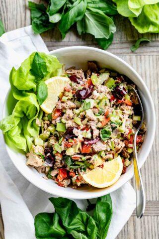 Mediterranean tuna salad in a white bowl with lemon wedges