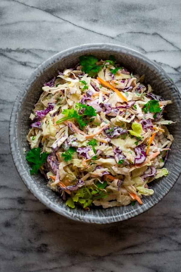 Skinny Classic Coleslaw with shredded carrots, purple and green cabbage and creamy greek yogurt dressing. This is the perfect healthy side salad for your summer picnics, cookouts and barbecues. Naturally gluten-free and primal. By Katie Webster on HealthySeasonalRecipes.com