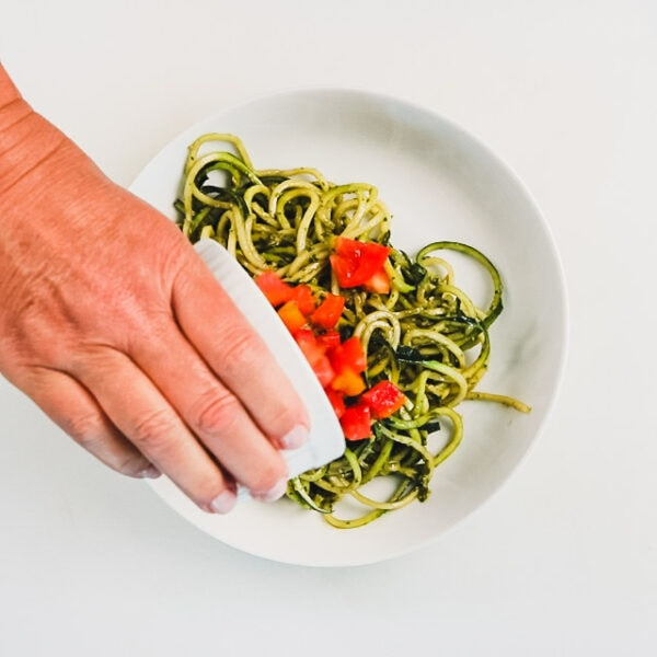 Transfer the zucchini noodles to a serving dish. Top the noodles with chopped tomatoes.
