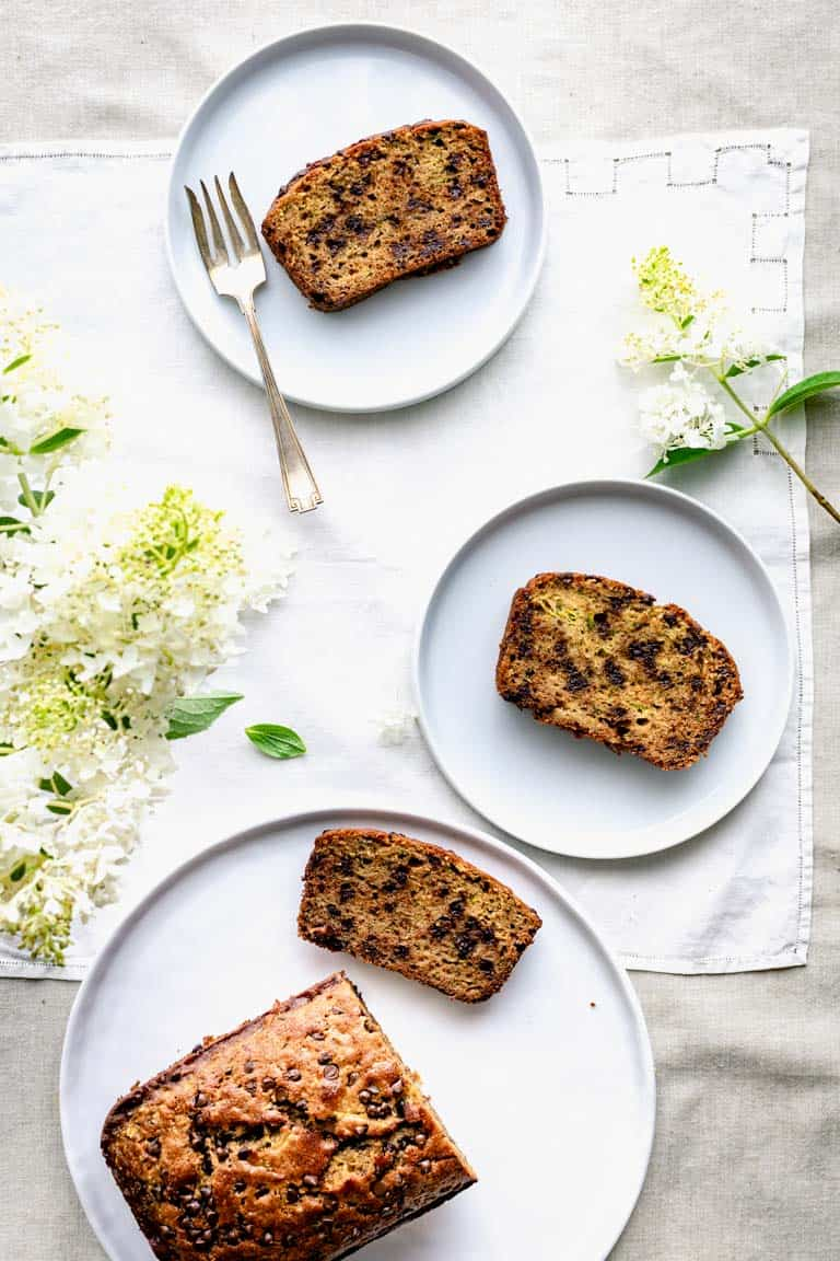 overhead of a white table with slices of zucchini chocolate chip bread