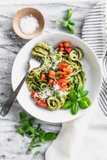 Zucchini Noodles with tomatoes on top in a white bowl.
