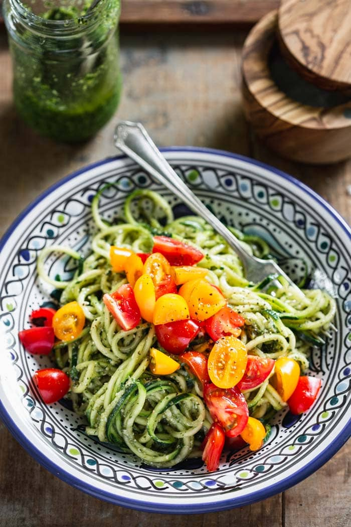 a blue bowl with a pile of green pesto zoodles with a fork in it