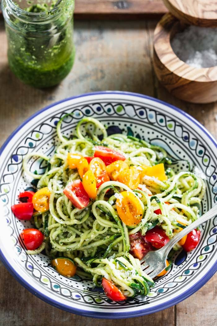 A blue and white plate with zucchini noodles topped with colorful cherry tomatoes