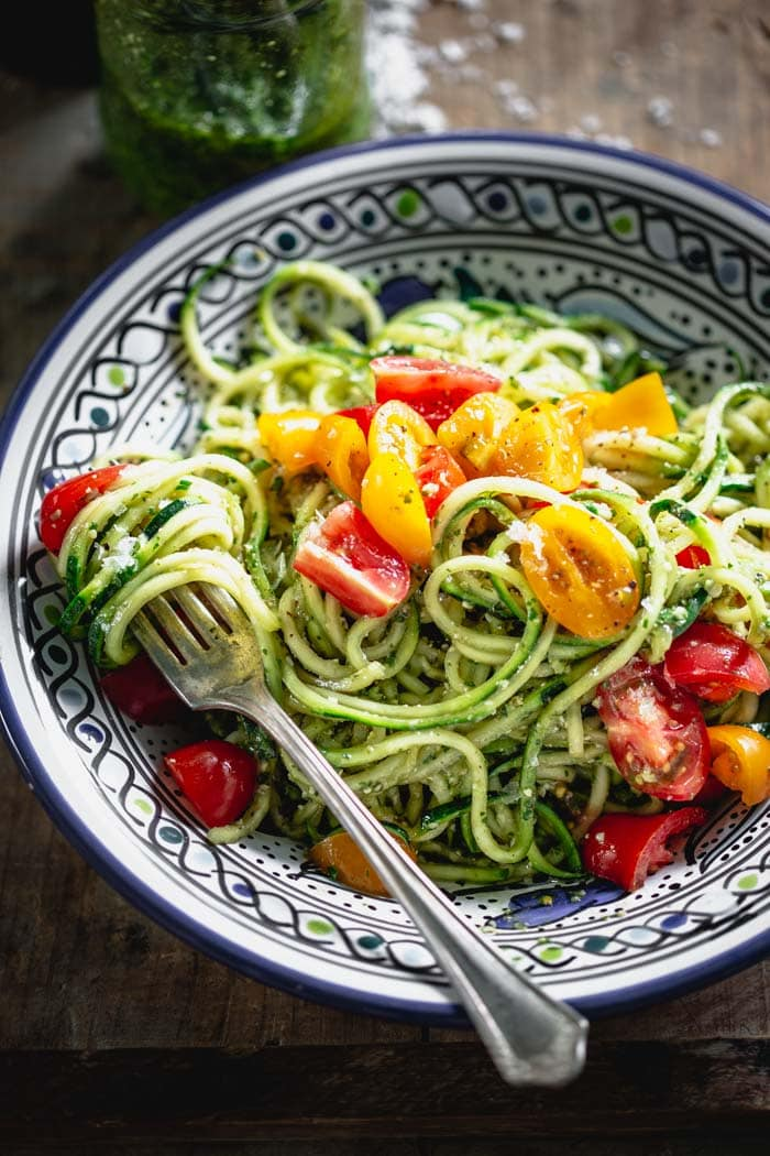 zucchini noodles with pesto in a blue bowl