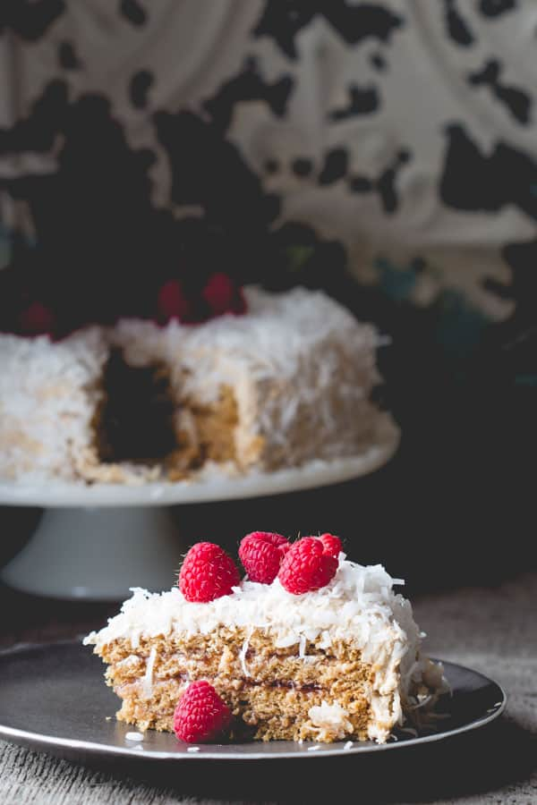 Coconut Raspberry Greek Yogurt Layer Cake by Healthy Seasonal Recipes is made with fat free Greek yogurt in the batter and the light cream cheese frosting to make it healthier.