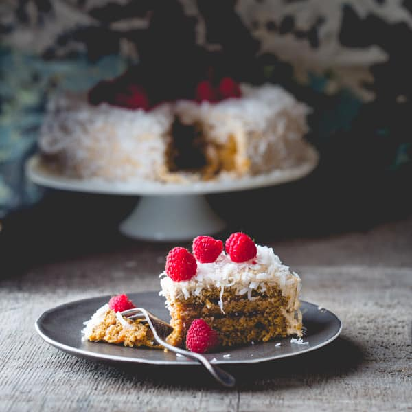 This coconut covered layer cake with layers of raspberry jam topped ...